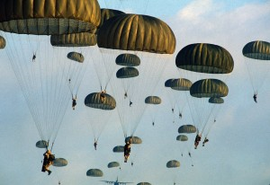 Members of the 82nd Airborne Division parachute from a C-130 Hercules aircraft during the joint Exercise BRIGHT STAR '83.